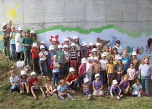 A number of children in front of a wall