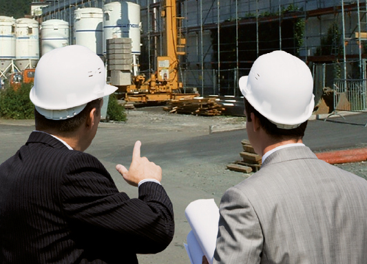 Two men speaking with one another and pointing to a maxit factory
